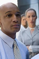 Close_up of a businessman looking serious with two businesswomen in the background