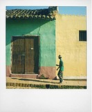 Polaroid of man walking along street against houses painted green and yellow, Trinidad, Cuba, West Indies, Central America