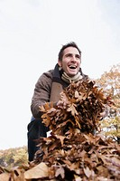 Low angle view of a young man holding leaves and laughing