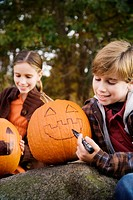 Boy drawing a human face on a pumpkin with his sister sitting behind him