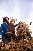 Low angle view of a family playing with leaves