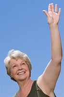 Low angle view of a senior woman waving her hand