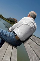 Rear view of a senior man sitting on a bench at the lakeside and fishing