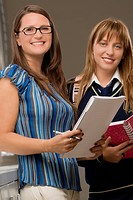 Portrait of a teenage girl standing with her female teacher and smiling (thumbnail)