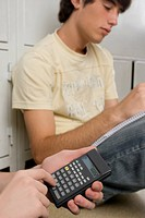 Close_up of a person's hand using a calculator and a young man sitting beside him