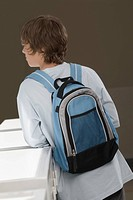 Rear view of a teenage boy carrying a backpack