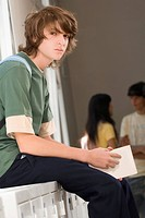 Portrait of a teenage boy sitting on a cabinet and looking serious (thumbnail)