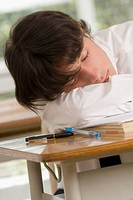 Close_up of a young man sleeping on desk in a classroom