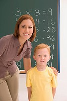 Portrait of a schoolboy standing with his female teacher in a classroom