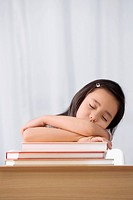 Schoolgirl sleeping at a desk in a classroom