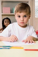 Portrait of a boy drawing on a sheet of paper with a girl sitting behind him