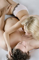 High angle view of a young couple lying on the bed and romancing