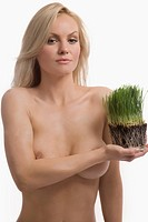 Portrait of a young woman holding wheatgrass