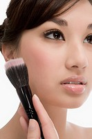 Close_up of a young woman holding a make_up brush and thinking