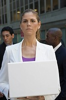 Close_up of a businesswoman holding a laptop with two businessmen standing behind her