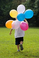 Rear view of a boy holding balloons and running in a playground