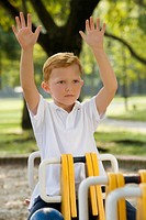 Boy sitting on a ride with his arms raised in a park