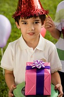 Boy holding a birthday present and smiling