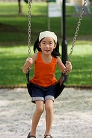 Girl swinging on a chain swing ride and smiling