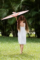 Rear view of a girl walking in a park with an umbrella