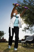 Low angle view of a senior woman exercising with dumbbells in a park