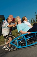Two senior women sitting on a quadracycle and two senior men pushing it