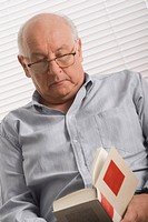 Close_up of a senior man reading a book