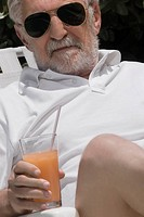 Close_up of a senior man holding a glass of juice
