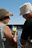 Rear view of a senior couple sitting at the lakeside (thumbnail)