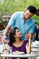 Couple looking at each other and smiling at a sidewalk cafe