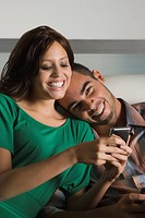 Young woman using a mobile phone and a young man leaning on her shoulder
