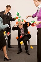Businessman protecting himself from colleagues throwing paper balls