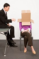Businesswoman covering her face with a cardboard box and a businessman sitting beside her on a desk