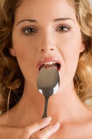 Portrait of a young woman with a spoon in her mouth