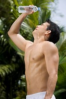 Side profile of a young man pouring water on his face