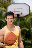 Portrait of a young man holding a basketball and smiling