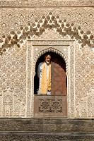 Man wearing traditional cloth looks out of a window decorated with rich ornaments Medersa Bou Inania Fes El_Bali Morocco