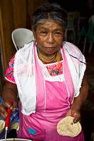 Portrait of a senior woman holding tortilla and cooking, Cuetzalan, Puebla State, Mexico