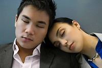 Businessman and a businesswoman sleeping at an airport
