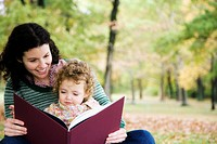Mid adult woman looking at a picture book with her daughter