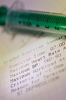 Close_up of a syringe on an electrocardiogram report