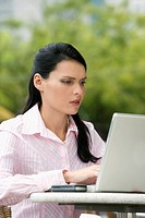 Close_up of a businesswoman using a laptop at a sidewalk cafe