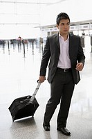 Businessman pulling his luggage at an airport