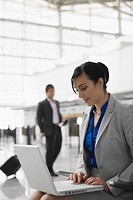 Businesswoman sitting at an airport and using a laptop