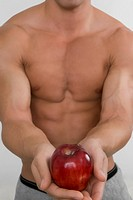 Mid section view of a man holding an apple