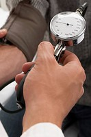 Close_up of a person´s hand checking a patient´s blood pressure