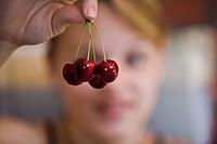 girl holds cluster of cherries between her fingers