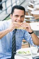 Portrait of a businessman eating a cheese sandwich