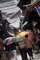 Locals with umbrellas in rain, Lijiang old town, UNESCO World Heritage Site, Yunnan, China, Asia