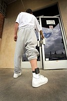 Wearing an electronic ankle monitor, a teenage offender enters a county parole facility in Santa Ana, CA. An ankle monitor is a device that individual...